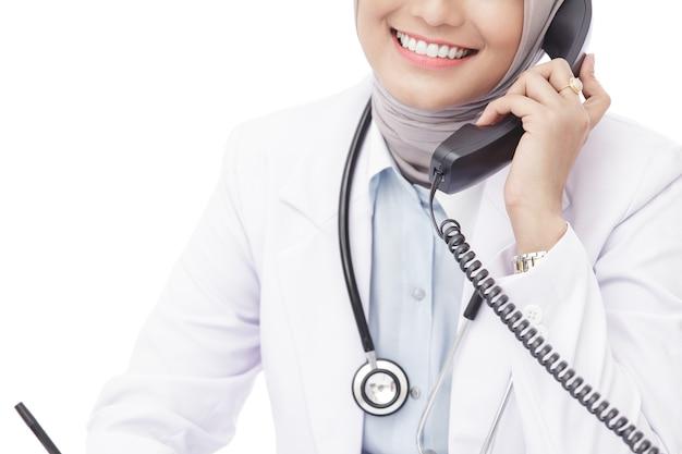 Feche o retrato de uma médica asiática com um estetoscópio falando ao telefone