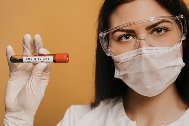Feche o retrato de uma médica em máscara cirúrgica, luvas e óculos de proteção mantém um tubo de ensaio com um teste covid-19 de coronavírus. conceito de médicos, infectologista, pesquisa e covid19.