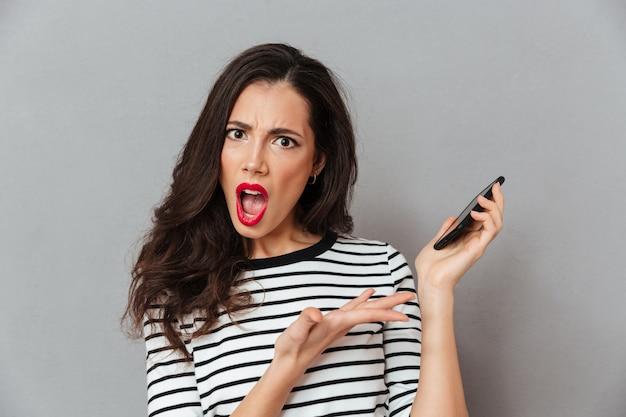Feche o retrato de uma menina chocada, segurando o telefone móvel