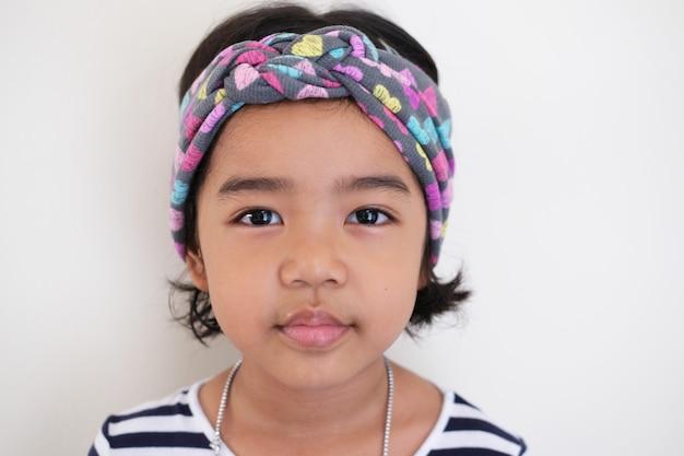 Feche o retrato de uma menina criança asiática usando bandana