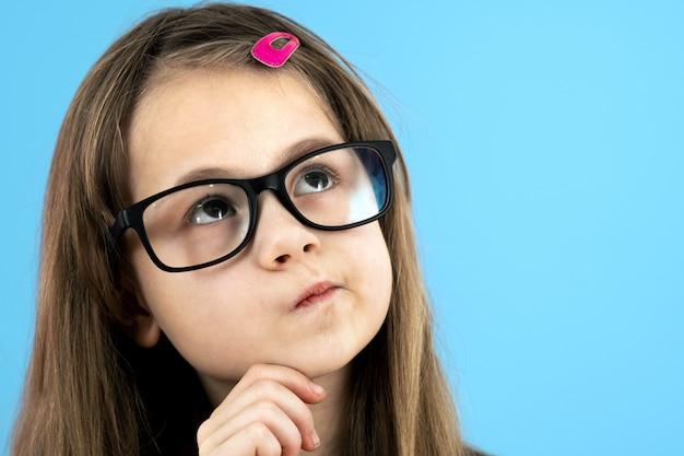 Feche o retrato de uma menina da escola infantil de óculos, segurando a mão no rosto, pensando em algo isolado sobre fundo azul.