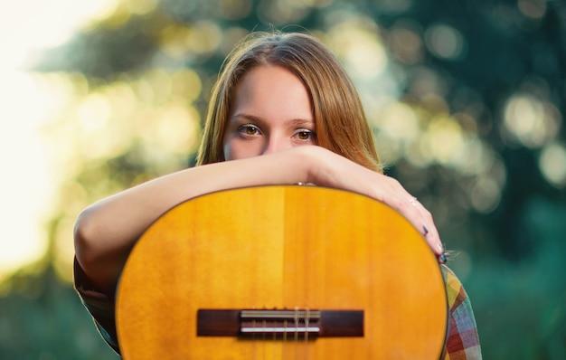 Feche o retrato de uma menina músico com um violão acústico de madeira