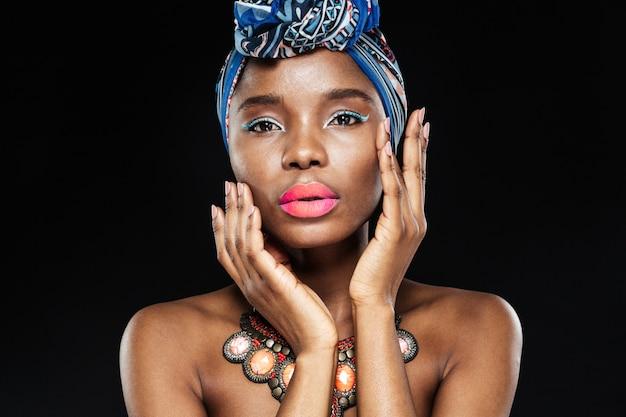 Feche o retrato de uma modelo feminina posando com as mãos no rosto isoladas na parede preta