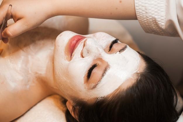 Feche o retrato de uma morena encantadora inclinada sobre uma cama com os olhos fechados, tendo uma rotina de cuidados com a pele com máscara branca em um centro de bem-estar.