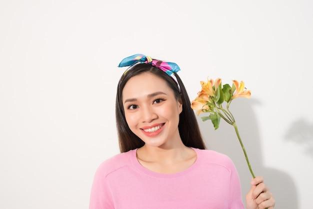 Feche o retrato de uma mulher adorável, linda e fofa em roupas casuais com um sorriso radiante e longos cabelos loiros, segurando três flores perto da bochecha, em pé