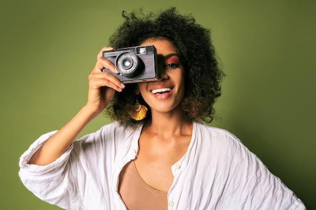 Feche o retrato de uma mulher afican segurando a câmera fotográfica retrô e rindo.