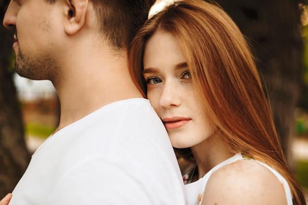 Feche o retrato de uma mulher atraente de cabelos vermelhos com sardas olhando diretamente séria enquanto inclina a cabeça para o lado de fora do namorado.
