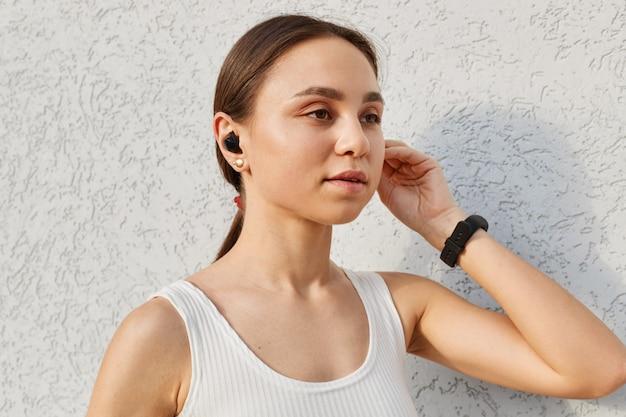 Feche o retrato de uma mulher atraente, vestindo top esportivo branco usando airpods para ouvir música ou podcast durante o treinamento ao ar livre, posando isolado sobre a parede de luz ao ar livre.