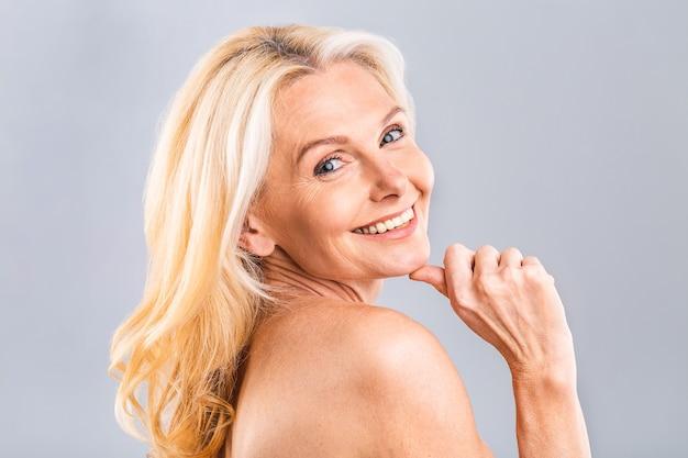 Feche o retrato de uma mulher bonita, atraente, charmosa, nua, nua tocando sua pele perfeita, isolada no fundo branco, após o banho, peeling, loção, máscara, bem-estar, conceito de hidratação.