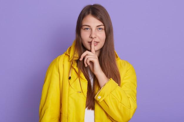 Feche o retrato de uma mulher bonita atraente e fofa segurando o dedo indicador perto dos lábios isolados em um fundo lilás, tem uma expressão facial confiante, vestindo uma jaqueta amarela brilhante, mantém informações secretas.