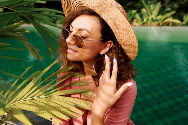 Feche o retrato de uma mulher bonita com cabelos cacheados no chapéu de palha posando perto da piscina.