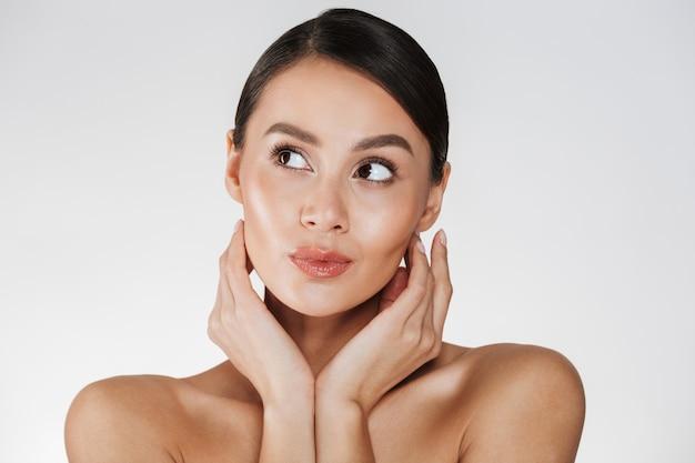 Feche o retrato de uma mulher bonita com maquiagem natural, olhando de lado e segurando as mãos perto de seu rosto saudável, isolado sobre o branco