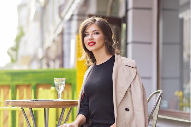 Feche o retrato de uma mulher bonita e charmosa com lábios vermelhos, usando um vestido preto e um casaco bege, descansando em um refeitório de verão com um copo d'água