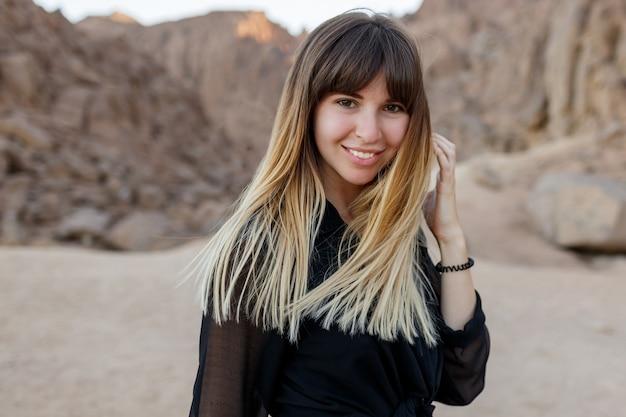 Feche o retrato de uma mulher bonita nas dunas de areia do deserto egípcio.