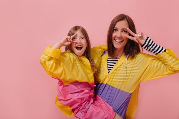 Feche o retrato de uma mulher bonita vestindo uma capa de chuva brilhante, segurando sua filha encantadora e mostrando o símbolo da paz