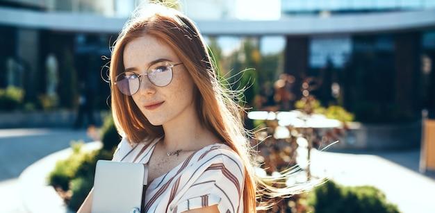 Feche o retrato de uma mulher caucasiana com cabelo ruivo e sardas, usando óculos e posando com um laptop em um dia ensolarado de vento