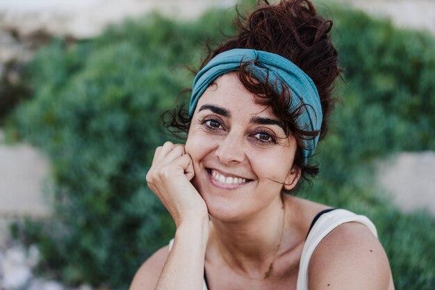 Feche o retrato de uma mulher caucasiana feliz, sorrindo na frente de uma vegetação verde durante o verão. estilo de vida ao ar livre