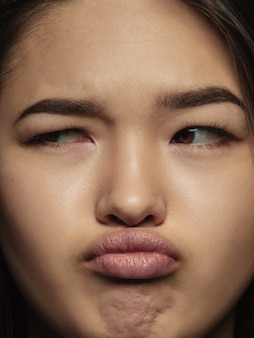 Feche o retrato de uma mulher chinesa jovem e emocional. foto fotográfica altamente detalhada da modelo feminina com uma pele bem cuidada e uma expressão facial brilhante. conceito de emoções humanas. pensando, olhando de lado.