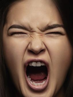 Feche o retrato de uma mulher chinesa jovem e emocional. sessão de fotos altamente detalhada de modelo feminino com pele bem cuidada e expressão facial brilhante. conceito de emoções humanas. gritos de raiva.