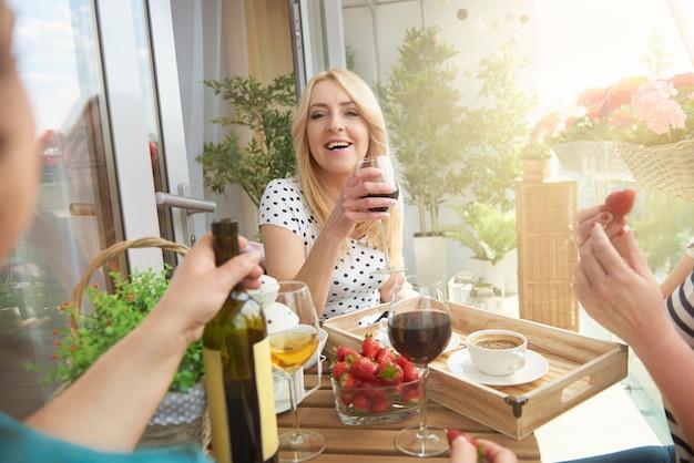 Feche o retrato de uma mulher com vinho na varanda