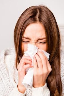 Feche o retrato de uma mulher doente com febre espirrando no tecido
