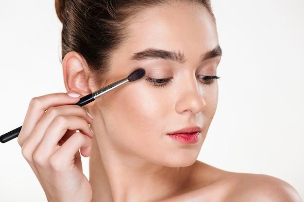 Feche o retrato de uma mulher elegante com pele limpa brilhante, aplicando sombra para os olhos usando o pincel