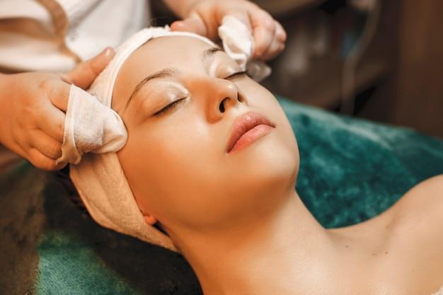 Feche o retrato de uma mulher encantadora encostada em uma cama de spa com os olhos fechados, tendo os procedimentos de cuidados da pele em um centro de bem-estar.
