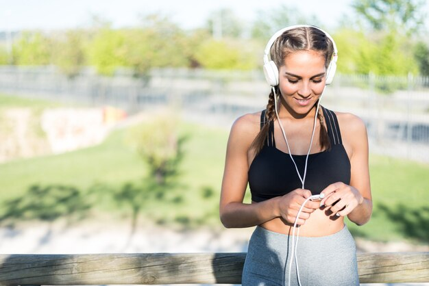Feche o retrato de uma mulher fazendo esporte descansando ao ar livre, sorrindo e ouvindo música