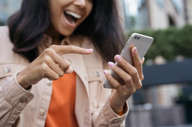 Feche o retrato de uma mulher feliz e emocional usando aplicativo móvel, compras online, apostas esportivas