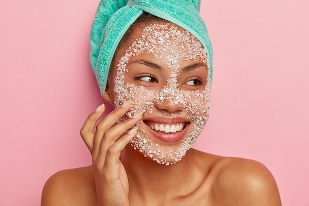 Feche o retrato de uma mulher feliz massageando as bochechas, aplica esfoliante com sal marinho, desvia o olhar, tem um sorriso gentil, mostra os dentes brancos, usa toalha turquesa, feliz por receber tratamentos de spa.