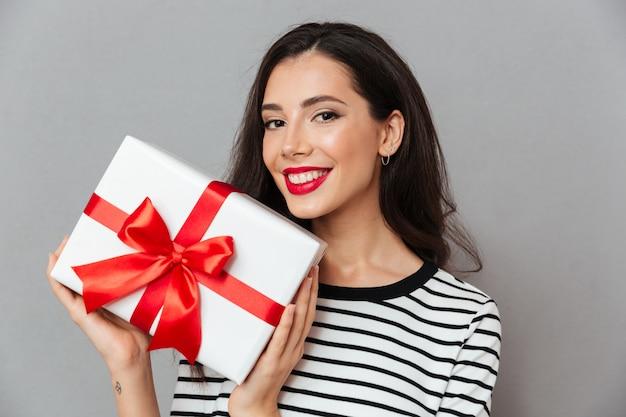 Feche o retrato de uma mulher feliz, segurando a caixa de presente