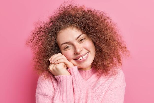 Feche o retrato de uma mulher gentil e satisfeita mantém as mãos perto do rosto sorri agradavelmente inclina a cabeça olha com ternura mostra os dentes admira algo usa jumper casual poses indoor contra parede rosa
