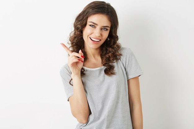 Feche o retrato de uma mulher jovem e atraente com expressão facial sorridente, segurando o dedo, mostrando de lado, beleza natural, camiseta, dentes brancos, isolado no fundo branco, gesticulando