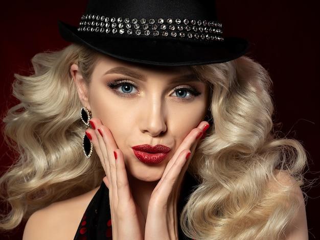 Feche o retrato de uma mulher jovem e bonita com maquiagem fashion. bela maquiagem de noite - olhos dourados esfumados e lábios vermelhos com brilhos.