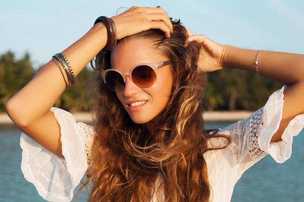 Feche o retrato de uma mulher linda em um vestido branco na praia tropical no pôr do sol, usando óculos escuros elegantes.