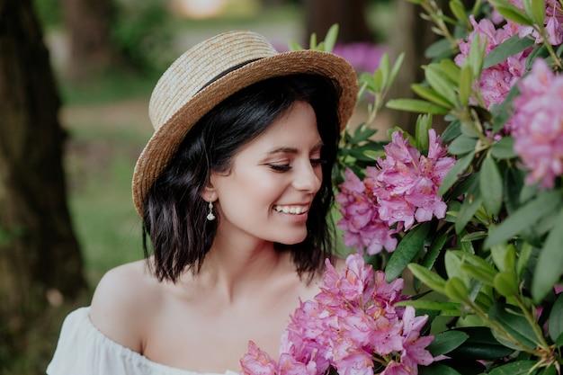 Feche o retrato de uma mulher linda em um vestido branco vintage e chapéu de palha em pé perto de flores cor de rosa