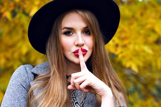 Feche o retrato de uma mulher loira bonita elegante posando em um dia frio de outono no parque da cidade, usando um elegante chapéu preto, cabelos longos, maquiagem brilhante