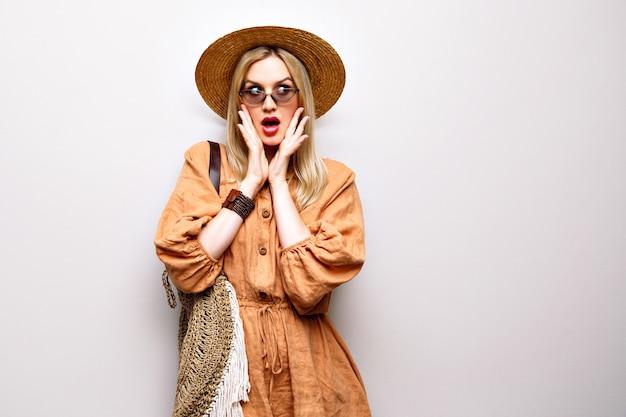 Feche o retrato de uma mulher loira bonita usando chapéu de palha e roupa boho