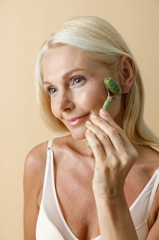 Feche o retrato de uma mulher loira madura com a pele brilhante sorrindo de lado enquanto usa o tratamento facial de jade