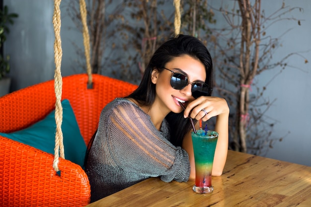 Feche o retrato de uma mulher morena bonita feliz bebendo um coquetel frio saboroso, roupa elegante e óculos de sol espelhados, aproveite o fim de semana, a hora da festa.