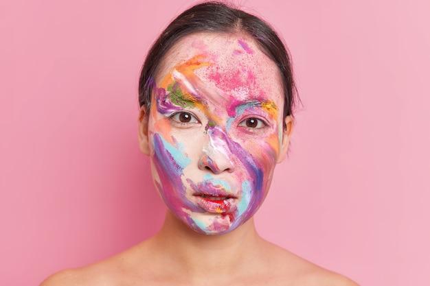 Feche o retrato de uma mulher morena séria com manchas de pintura de maquiagem criativa multicolorida no rosto