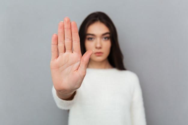 Feche o retrato de uma mulher mostrando o gesto de parada
