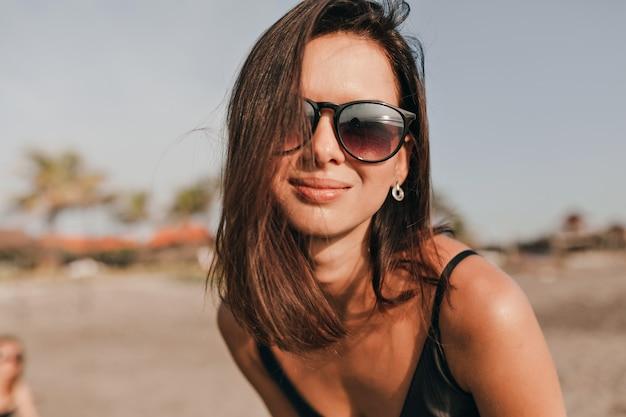 Feche o retrato de uma mulher muito feliz com cabelo escuro, usando óculos escuros pretos, posando durante a sessão de fotos na praia perto do oceano