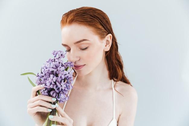 Feche o retrato de uma mulher ruiva cheirando flores jacintos