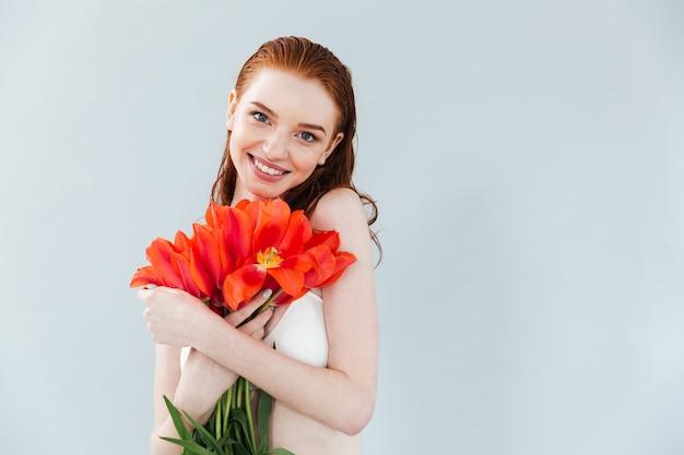 Feche o retrato de uma mulher ruiva segurando flores tulipa