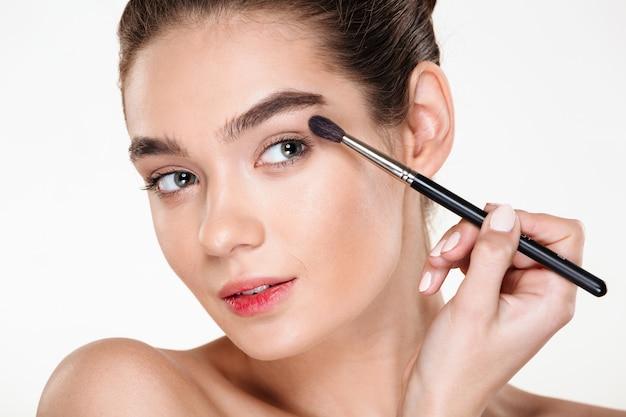 Feche o retrato de uma mulher sensual, com pele limpa brilhante, aplicando sombra para os olhos usando o pincel