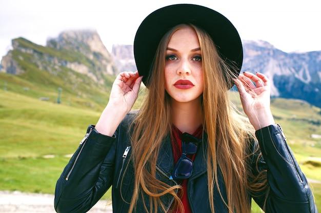Feche o retrato de uma mulher sensual posando nas montanhas alp, grandes olhos verdes e cabelos longos, usando um chapéu preto moderno e jaqueta de couro, cores enfraquecidas.
