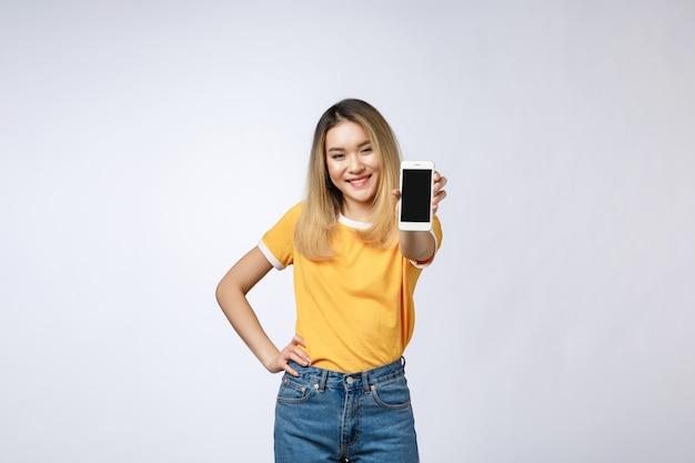 Feche o retrato de uma mulher sorridente asiática mostrando um celular com tela em branco