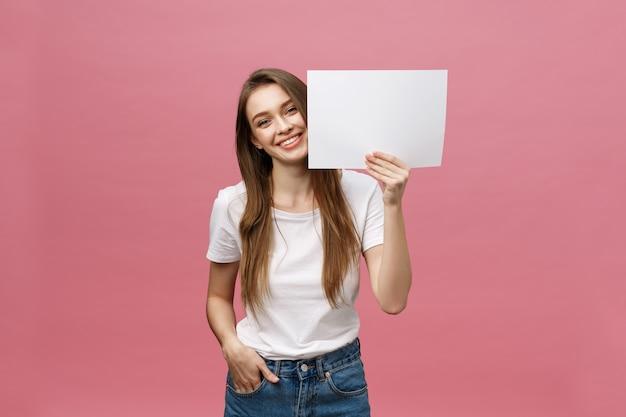 Feche o retrato de uma mulher sorridente e sorridente, segurando um pôster branco de maquete grande