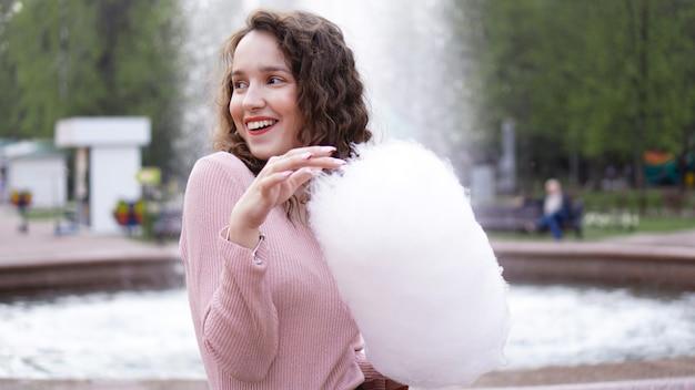 Feche o retrato de uma mulher sorridente feliz e animada segurando algodão doce no parque de diversões